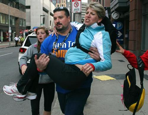 Former New England Patriots player Joe Andruzzi carries a woman from the scene on Exeter Street after two explosions went off on Boylston Street near the finish line of the 117th Boston Marathon, April 15, 2013. (Bill Greene/The Boston Globe/Getty Images)